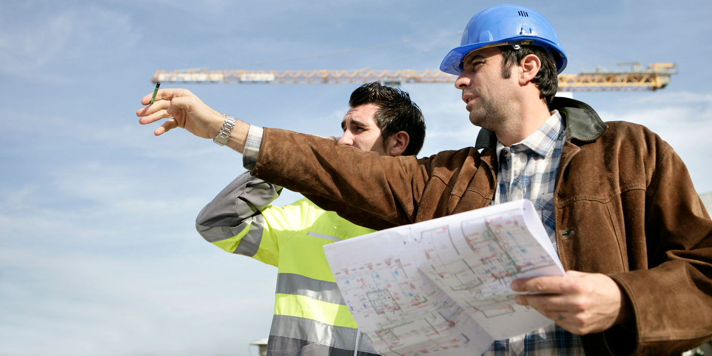 2 men looking over building site with blue print in the hand